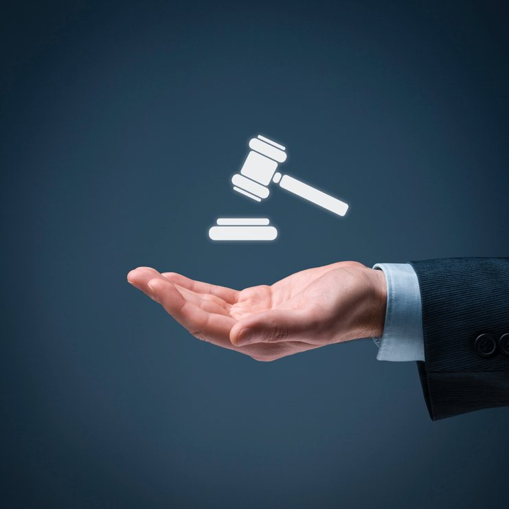 image of a legal gavel suspended over the hand of a lawyer to serve as a visual representation of the legal document services that PrintLegal.ca of Toronto offers